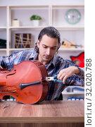 Купить «Young handsome repairman repairing cello», фото № 32020788, снято 4 апреля 2019 г. (c) Elnur / Фотобанк Лори