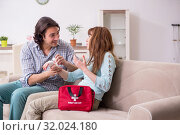 Купить «Young couple in first aid concept at home», фото № 32024180, снято 10 мая 2019 г. (c) Elnur / Фотобанк Лори