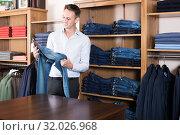 Купить «Ordinary guy deciding on new trousers», фото № 32026968, снято 28 марта 2017 г. (c) Яков Филимонов / Фотобанк Лори
