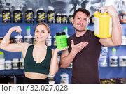 Купить «Happy athletic people with sport supplements showing muscles in store», фото № 32027028, снято 12 апреля 2018 г. (c) Яков Филимонов / Фотобанк Лори