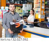 Купить «Man with purchases in household store», фото № 32027092, снято 17 мая 2018 г. (c) Яков Филимонов / Фотобанк Лори