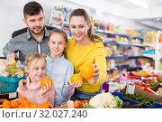 Купить «Family shopping together in greengrocery store choosing oranges», фото № 32027240, снято 20 января 2018 г. (c) Яков Филимонов / Фотобанк Лори