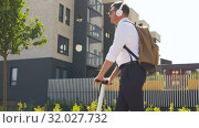 Купить «businessman with headphones riding scooter in city», видеоролик № 32027732, снято 5 августа 2019 г. (c) Syda Productions / Фотобанк Лори