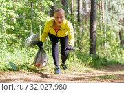 Female jogger leans over trash during plogging. Стоковое фото, фотограф Евгений Харитонов / Фотобанк Лори