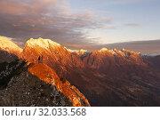 A hiker admires the sunset from the ridge of Dolada Mount, Prealps of Belluno, Pieve d'Alpago, Belluno province, Veneto, Italy. Стоковое фото, фотограф Clickalps SRLs / age Fotostock / Фотобанк Лори