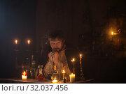 Купить «portrait of wizard with burning candles and magic potions», фото № 32037456, снято 14 августа 2019 г. (c) Майя Крученкова / Фотобанк Лори