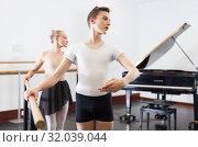 Купить «Choreographer woman and young man do exercises at ballet bar in hall with mirror», фото № 32039044, снято 26 апреля 2019 г. (c) Яков Филимонов / Фотобанк Лори