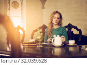 Young beautiful woman is sitting at the table and having dinner in the luxurious luxury interior. Стоковое фото, фотограф katalinks / Фотобанк Лори