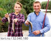 Купить «Man with teenager boy showing catch fish», фото № 32040180, снято 23 октября 2019 г. (c) Яков Филимонов / Фотобанк Лори