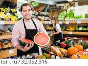 Купить «Young man seller holding half of watermelon in hands in fruit store», фото № 32052316, снято 27 апреля 2019 г. (c) Яков Филимонов / Фотобанк Лори