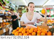 Купить «Young female choosing fresh oranges in fruit store», фото № 32052324, снято 27 апреля 2019 г. (c) Яков Филимонов / Фотобанк Лори