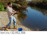 Купить «Adult man standing near river and pulling fish expressing emotions of dedication», фото № 32052356, снято 15 марта 2019 г. (c) Яков Филимонов / Фотобанк Лори