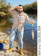 Купить «Adult man standing near river and pulling fish expressing emotions of dedication», фото № 32052364, снято 15 марта 2019 г. (c) Яков Филимонов / Фотобанк Лори