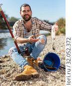 Купить «Bearded adult man posing with fish near river in summertime», фото № 32052372, снято 15 марта 2019 г. (c) Яков Филимонов / Фотобанк Лори