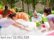 Купить «Friends picking up balls in inflatable pool with foam», фото № 32052520, снято 26 августа 2019 г. (c) Яков Филимонов / Фотобанк Лори