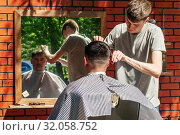 Купить «Orenburg, Russia - July, 20, 2019: Men's haircut in an open air salon. FORMA MARKET - a city festival for the promotion of handmade designers, artisans and their projects with the aim of engaging in the business environment», фото № 32058752, снято 20 июля 2019 г. (c) Вадим Орлов / Фотобанк Лори