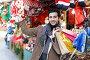 Купить «Smiling man choosing decorations at Christmas market», фото № 32059152, снято 4 декабря 2018 г. (c) Яков Филимонов / Фотобанк Лори