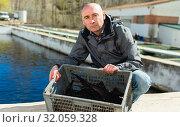 Купить «Fish farmer holding sturgeon», фото № 32059328, снято 19 марта 2019 г. (c) Яков Филимонов / Фотобанк Лори