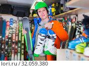 Купить «Portrait of adult man in jacket and helmet who is demonstrating ski and boots in store.», фото № 32059380, снято 31 июля 2017 г. (c) Яков Филимонов / Фотобанк Лори