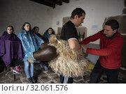 A young man prepares to participate as Joaldunak in the carnival of Ituren (Navarra) while they help him tie his bells. (2019 год). Редакционное фото, фотограф Joaquín Gómez / age Fotostock / Фотобанк Лори