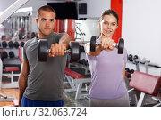 Sporty guy and girl posing with dumbbells. Стоковое фото, фотограф Яков Филимонов / Фотобанк Лори