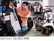 Купить «Man choosing jacket for moto», фото № 32063948, снято 1 сентября 2017 г. (c) Яков Филимонов / Фотобанк Лори
