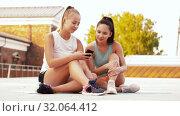 Купить «sporty women or friends with smartphone on rooftop», видеоролик № 32064412, снято 4 августа 2019 г. (c) Syda Productions / Фотобанк Лори