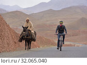 Encounter between an old man riding a mule and a cyclist with mountain pedelec on the road connecting Tizi n'Tichka pass to Telouet village, Ouarzazate... (2019 год). Редакционное фото, фотограф Christian Goupi / age Fotostock / Фотобанк Лори