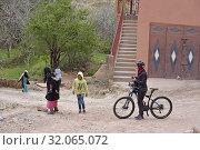 Biker crossing an hamlet near Tighza in the Ounila River valley, Ouarzazate Province, region of Draa-Tafilalet, Morocco, North West Africa. (2019 год). Редакционное фото, фотограф Christian Goupi / age Fotostock / Фотобанк Лори