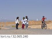 Biker overtaking students walking on a road through the reg, from Agdz to Zagora, Draa River valley, Province of Zagora, Region Draa-Tafilalet, Morocco, North West Africa. (2019 год). Редакционное фото, фотограф Christian Goupi / age Fotostock / Фотобанк Лори