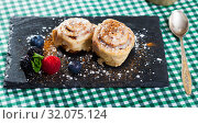 Купить «Tasty cinnamon rolls with fresh berries and powdered sugar at plate», фото № 32075124, снято 12 декабря 2019 г. (c) Яков Филимонов / Фотобанк Лори