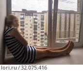 Десятилетняя девочка сидит на подоконнике. Стоковое фото, фотограф Вячеслав Палес / Фотобанк Лори