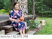 Portrait of smiling elderly woman with milk jug in hands, country house wooden veranda with pile of logs, copyspace. Стоковое фото, фотограф Кекяляйнен Андрей / Фотобанк Лори