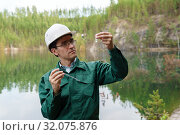Купить «Industrial ecologist visually evaluates the response of a water sample from lake at the site of a flooded quarry», фото № 32075876, снято 10 августа 2019 г. (c) Евгений Харитонов / Фотобанк Лори