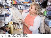 Купить «customer female choosing cotton tablecloths in the textile store», фото № 32076352, снято 29 ноября 2017 г. (c) Яков Филимонов / Фотобанк Лори