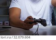 Купить «Young man playing games long hours late in the office», фото № 32079604, снято 5 июля 2017 г. (c) Elnur / Фотобанк Лори