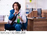 Купить «Young drunk employee in the office», фото № 32080264, снято 24 мая 2019 г. (c) Elnur / Фотобанк Лори