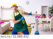 Купить «Young male contractor doing housework after party», фото № 32080432, снято 14 марта 2019 г. (c) Elnur / Фотобанк Лори