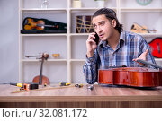 Купить «Young handsome repairman repairing cello», фото № 32081172, снято 4 апреля 2019 г. (c) Elnur / Фотобанк Лори