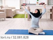 Купить «Young woman in hijab doing exercises at home», фото № 32081828, снято 18 марта 2019 г. (c) Elnur / Фотобанк Лори