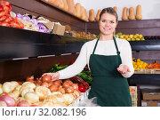 female seller in apron offering fresh greens and vegetables. Стоковое фото, фотограф Яков Филимонов / Фотобанк Лори