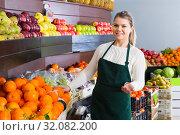 Купить «Young female in apron selling fresh oranges», фото № 32082200, снято 29 мая 2020 г. (c) Яков Филимонов / Фотобанк Лори