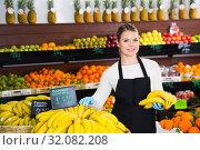 Купить «Young female seller in gloves selling fresh bananas on the market», фото № 32082208, снято 31 января 2019 г. (c) Яков Филимонов / Фотобанк Лори