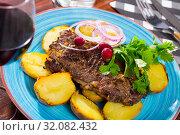 Купить «Beef steak with baked potatoes and sauce at plate with greens», фото № 32082432, снято 19 сентября 2019 г. (c) Яков Филимонов / Фотобанк Лори