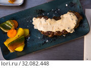 Купить «Prepared veal steak with fried potatoes and pepper sauce served», фото № 32082448, снято 19 сентября 2019 г. (c) Яков Филимонов / Фотобанк Лори