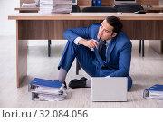 Купить «Young male employee and too many work in the office», фото № 32084056, снято 9 мая 2019 г. (c) Elnur / Фотобанк Лори
