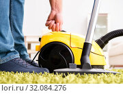 Man cleaning the floor carpet with a vacuum cleaner close up. Стоковое фото, фотограф Elnur / Фотобанк Лори