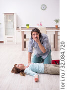 Купить «Young couple in first aid concept at home», фото № 32084720, снято 10 мая 2019 г. (c) Elnur / Фотобанк Лори