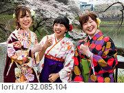 Japan, Honshu, Tokyo, Kudanshita, Chidori-ga-fuchi, Female University Students Dressed in Traditional Hakama Graduation Costumes with Cherry Blossom in Background. Стоковое фото, фотограф Steve Vidler / age Fotostock / Фотобанк Лори