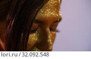 Woman with golden shining makeup. Стоковое видео, видеограф Илья Шаматура / Фотобанк Лори